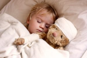 boy and teddybear in bed, with teddy bandaged